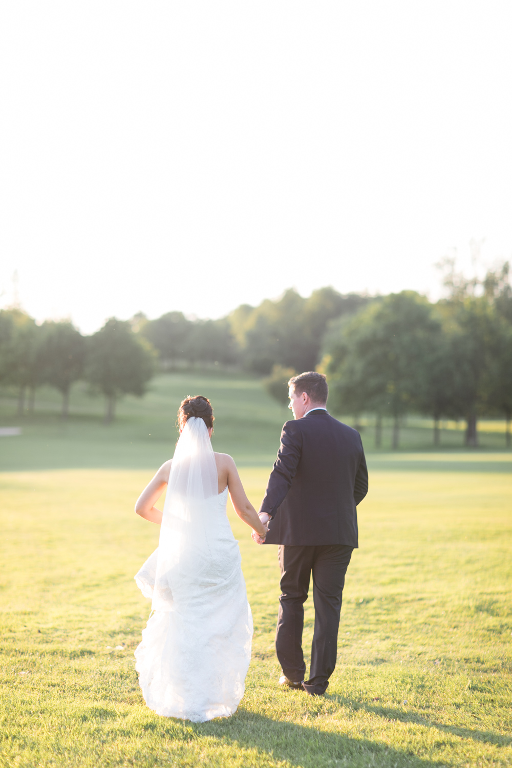 bride and groom are walking away from the camera hand in hand in the evening light down on the field of slieve russell hotel in ireland