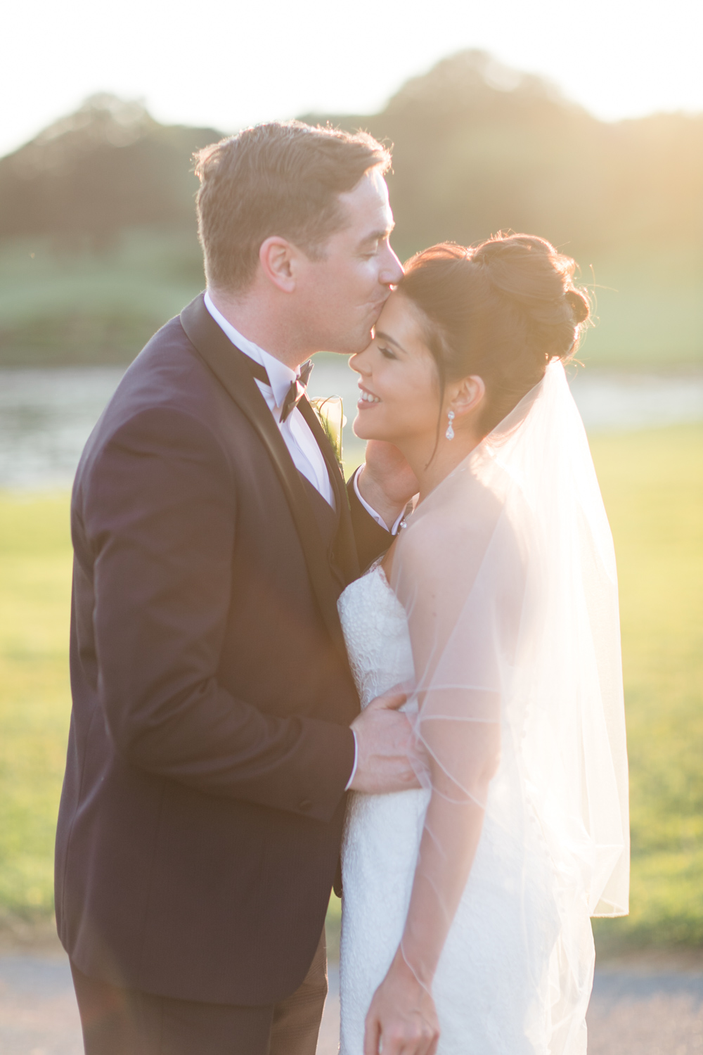 groom softly kissing the bride on the forhewad in the sunset of slieve russell hotel in ireland