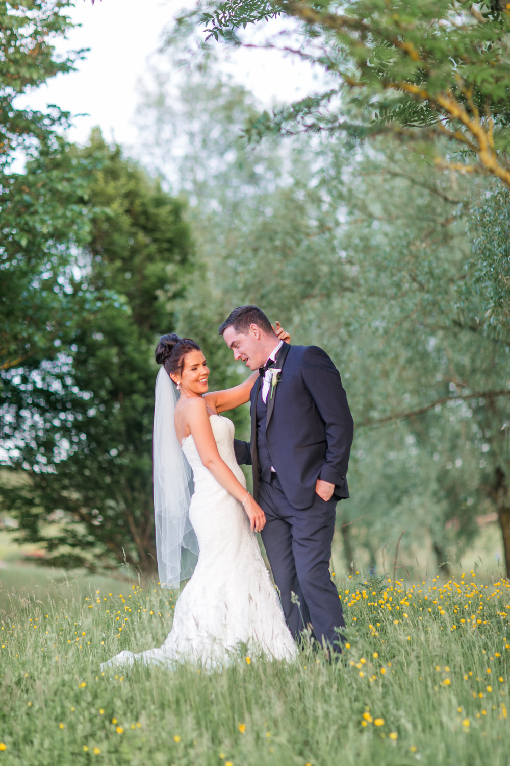 Bride and groom in a beautiful meadow posing for their wedding photographs