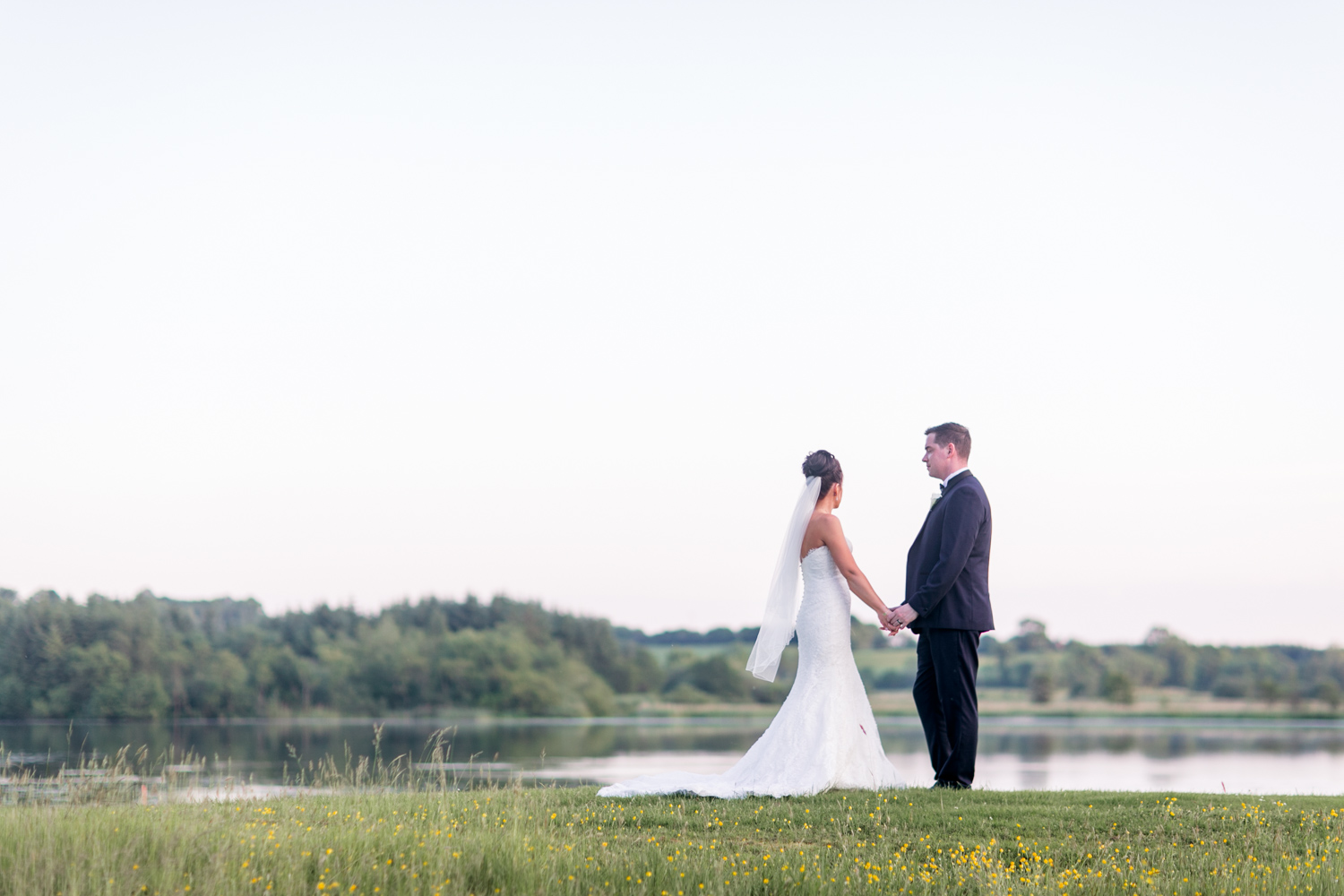 sun set photograph of bride and groom on the edge of a meadow and a lake at slieve russell hotel in ireland