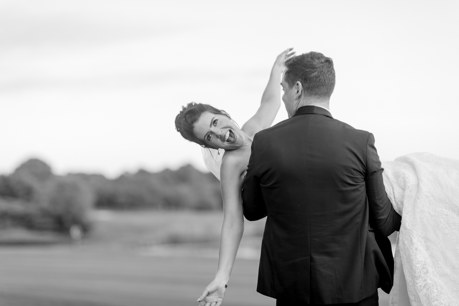 groom is carrying a happy laughing bride