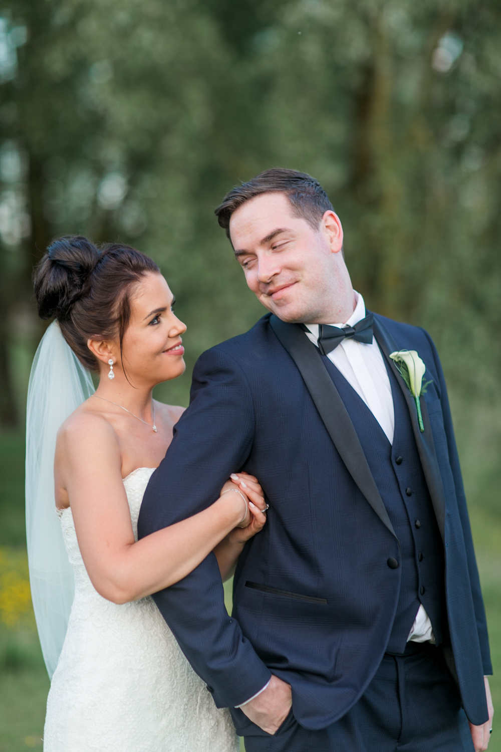 bridal portraits bride wrapped around the grooms hand they look at eachother at slieve russell hotel in ireland