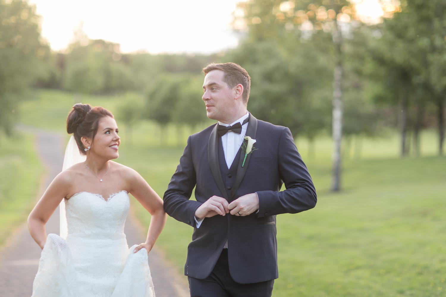 bride holding up her dress walking while groom is buttening his tux in the evening light