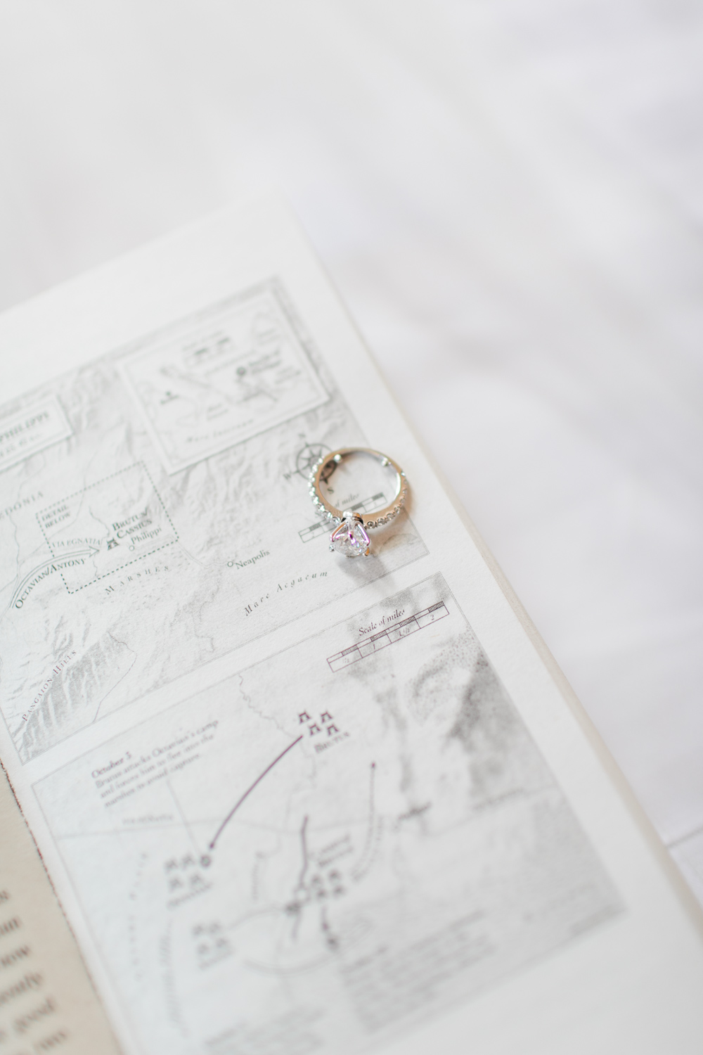 a white gold diamond ring on top of a map page in a book