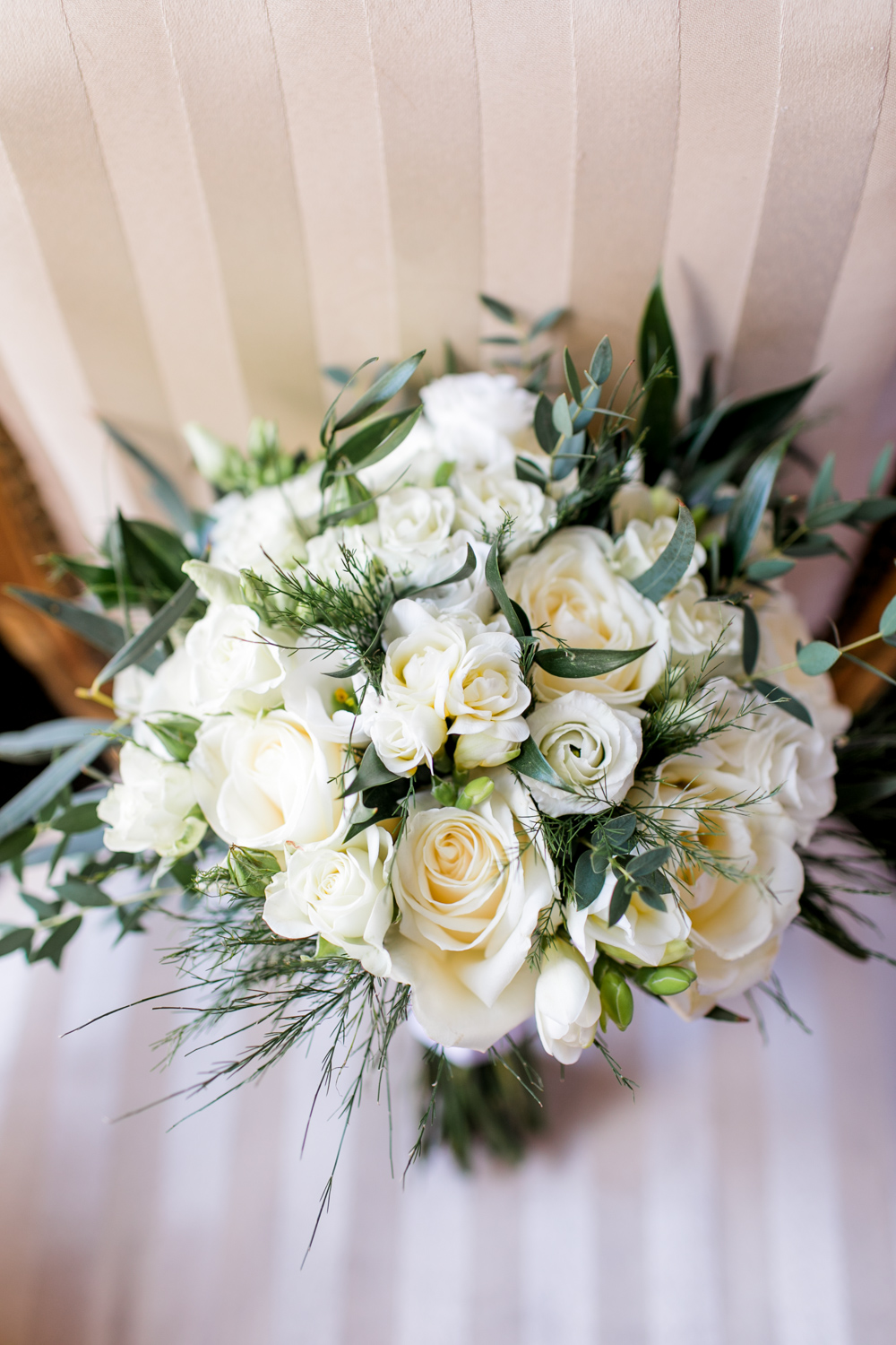 wedding flowers made out of white roses and white buttercups on a vintage chair