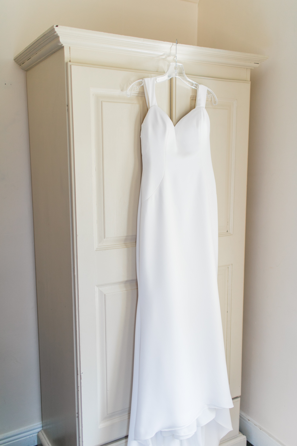 a white dress plain and elegant in design hanging in a hotel room off a white wardrobe