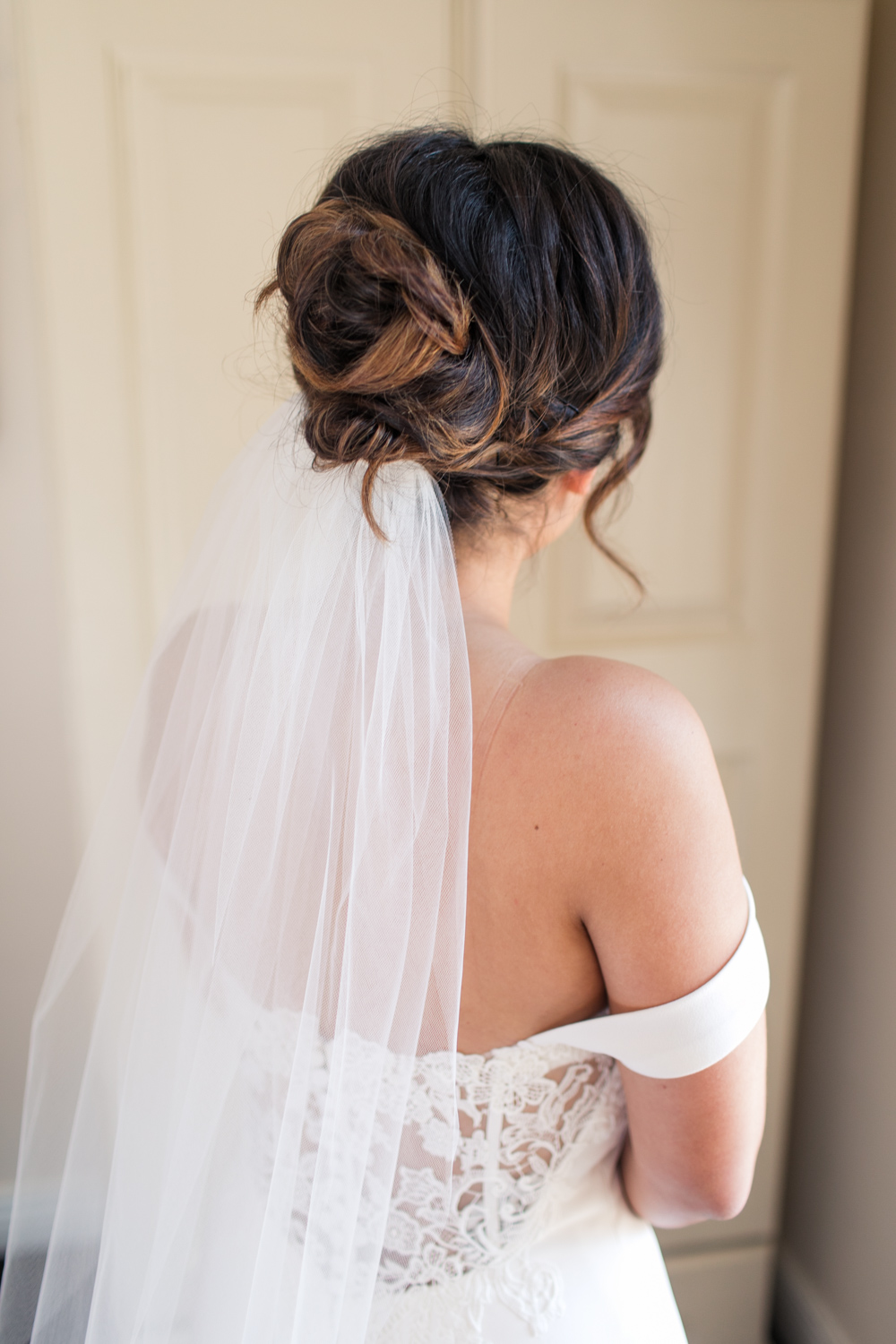 the back of the bride's dress featuring a hairdo in a bun with a veil attached to it