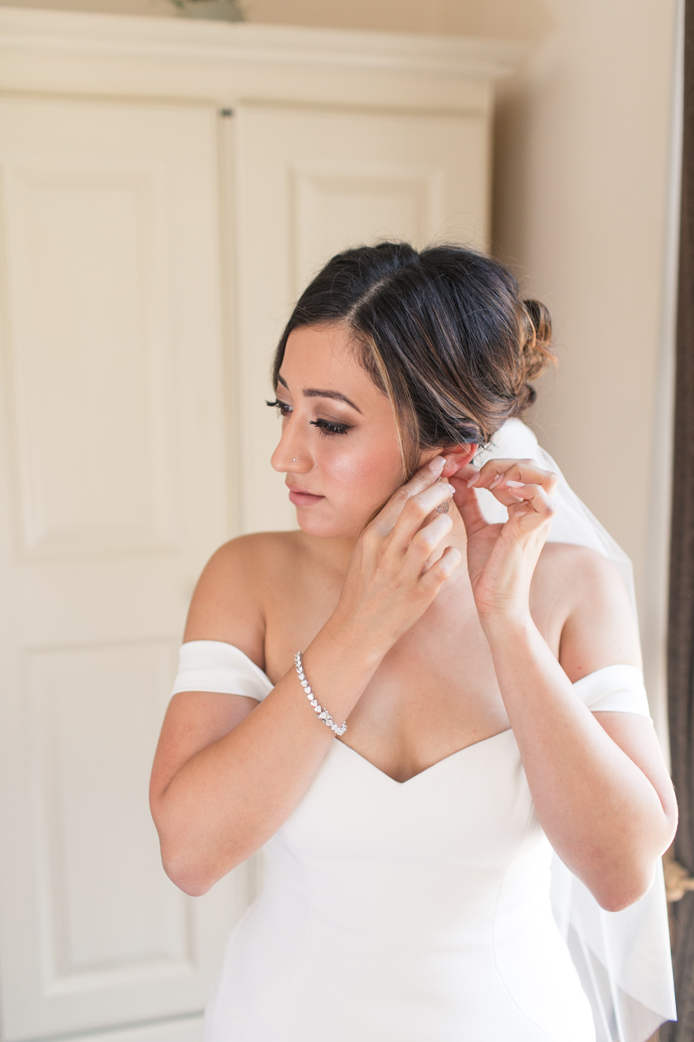 a portrait of a bride putting on her earrings in a dublin city centre hotel