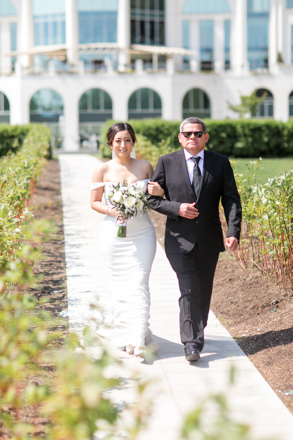 bride walking down the isle of the outside ceremony in a poerscourt hotel being escorted by her dad