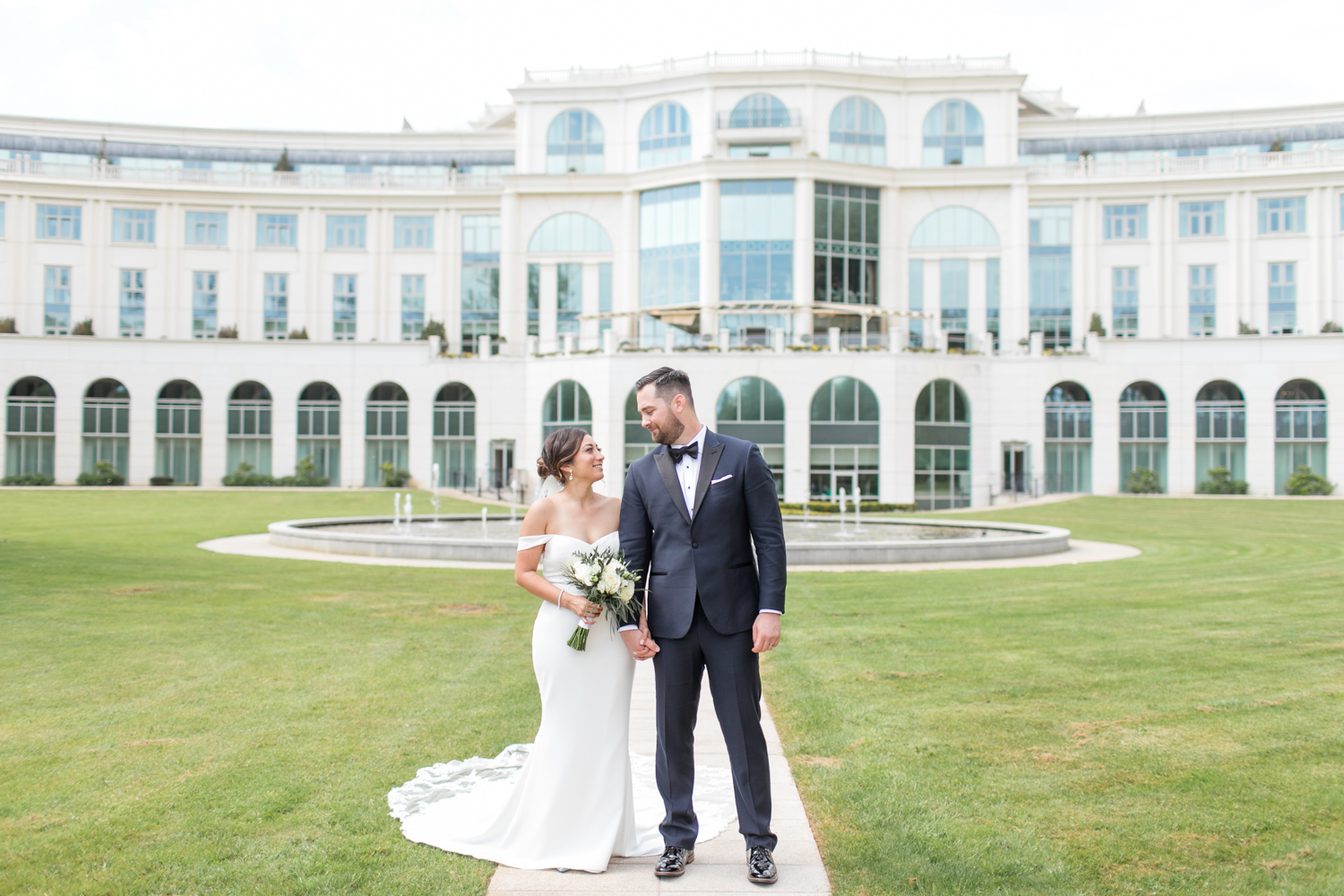 bride and groom posing in front of the powerscourt hotel located in wicklow, ireland