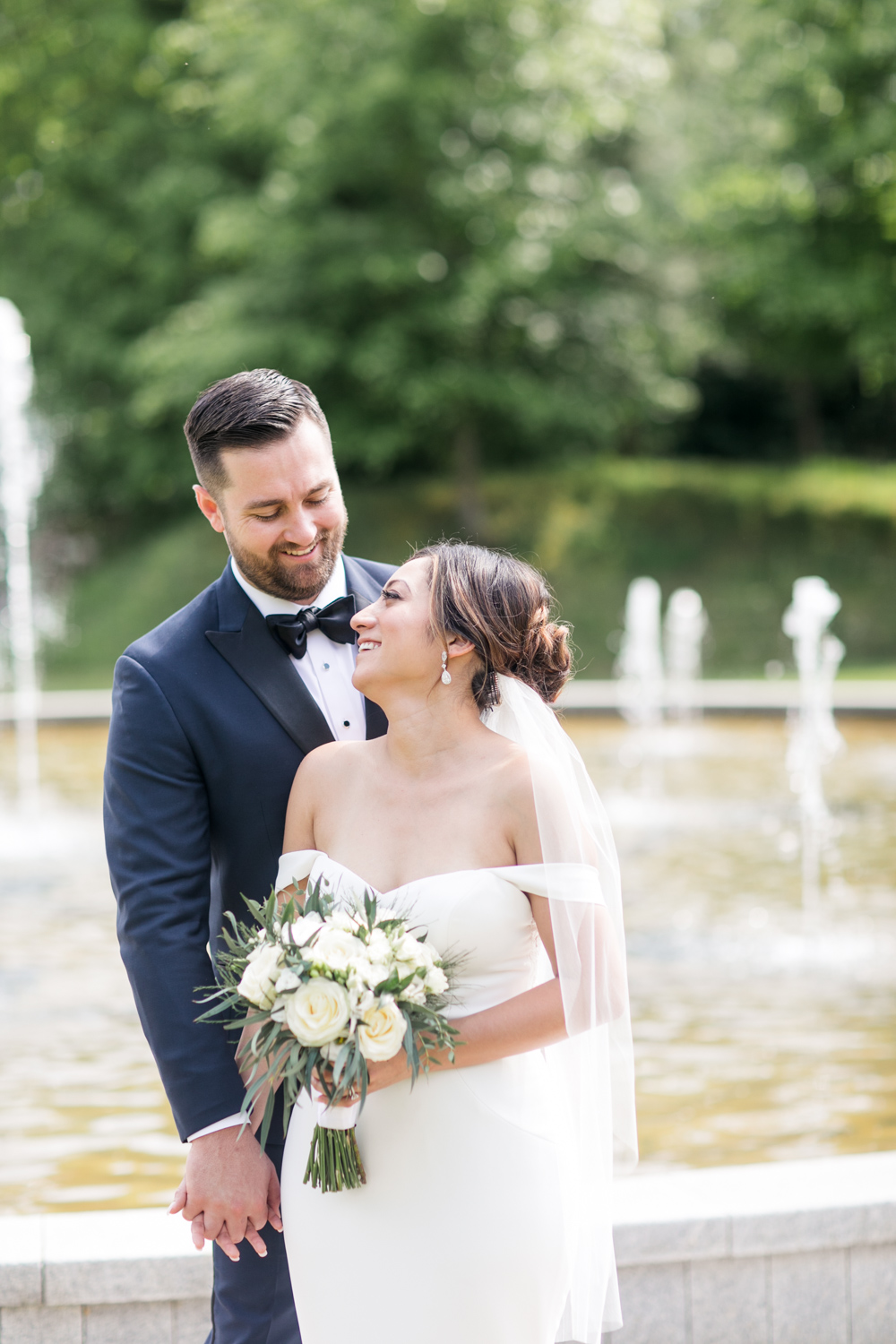 bride and groom looking at each other bride wearing an off shoulder white dress and groom wearing a black tie tux
