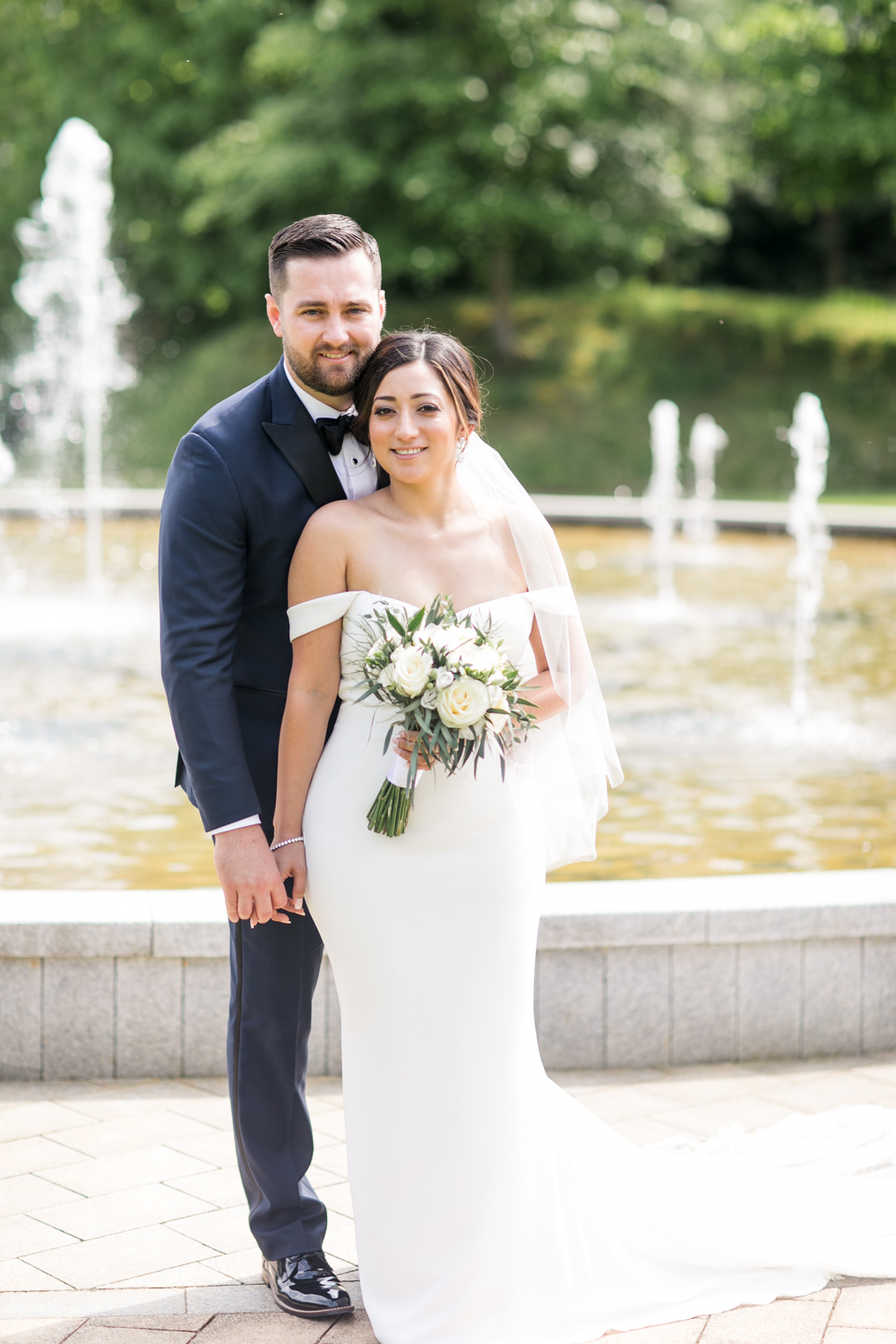 bride and groom standing beside each other on the grounds of powerscourt hotel holding hands wearing off shoulder plain wedding dress and black tie tux