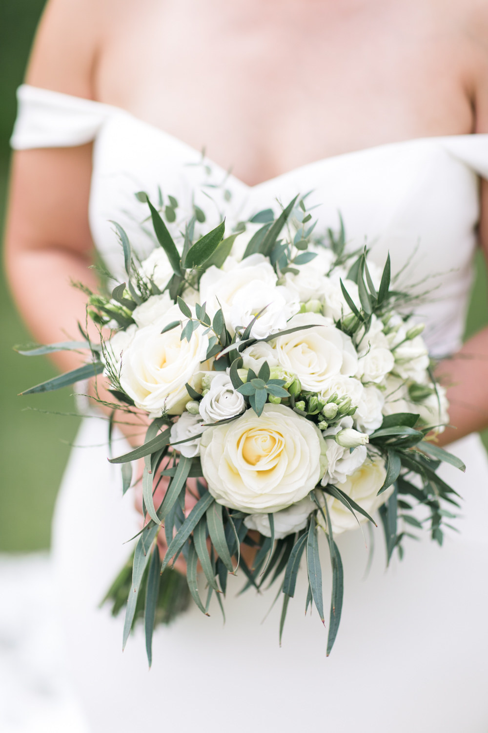 a close up of bride holding a bouquet of flowers with her off shoulder white wedding dress in the background