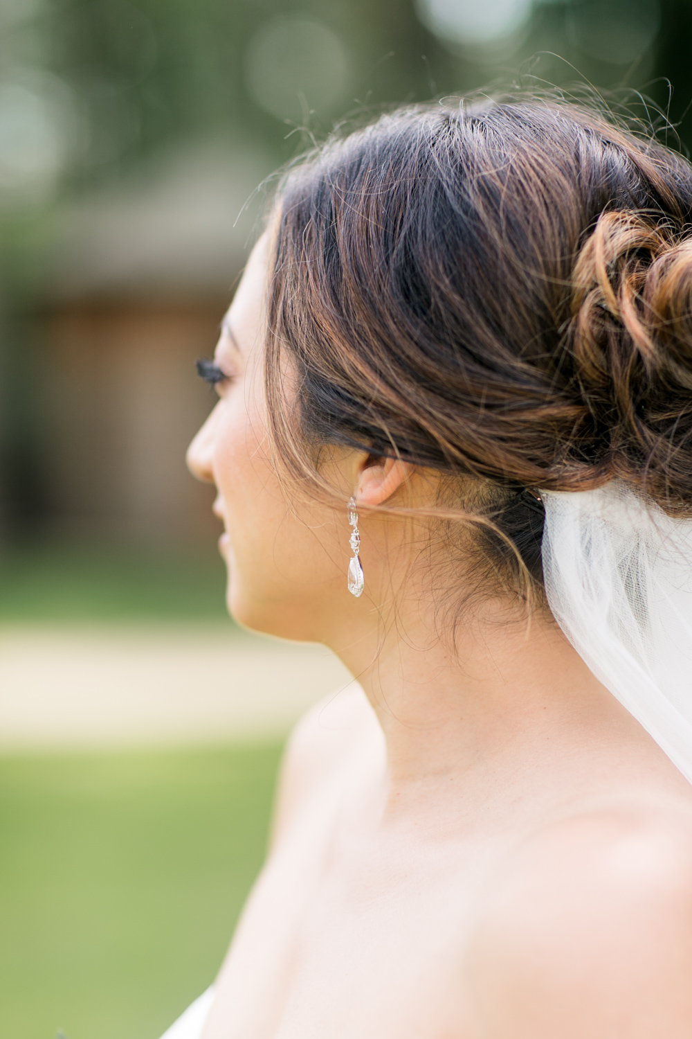 bride's earring detail showing off part of her up style hairdo bun and part of her veil and exposed shoulders
