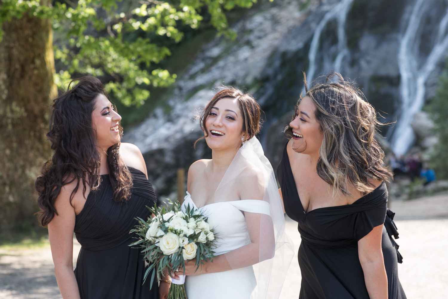 bride and her two bridesmaids wearing black dresses posing for the camera in front of the powerscourt waterfall in wicklow ireland