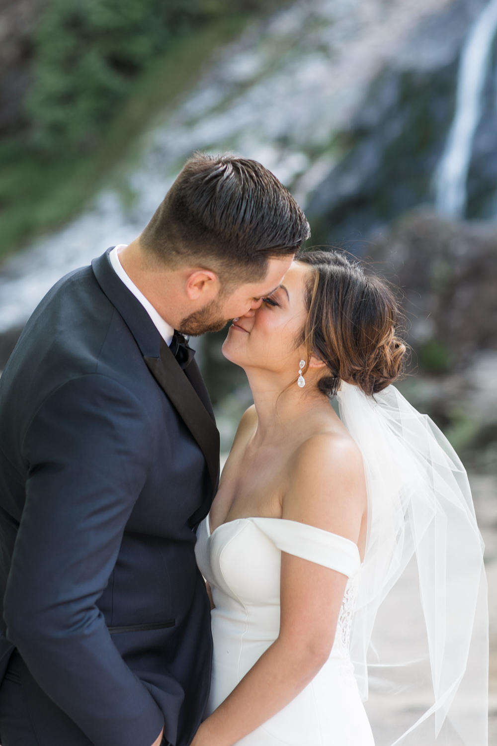 a close up shot of bride and groom nearly kissing each other groom wearing a black tie tux and bride wearing an off shoulder dress with a short veil