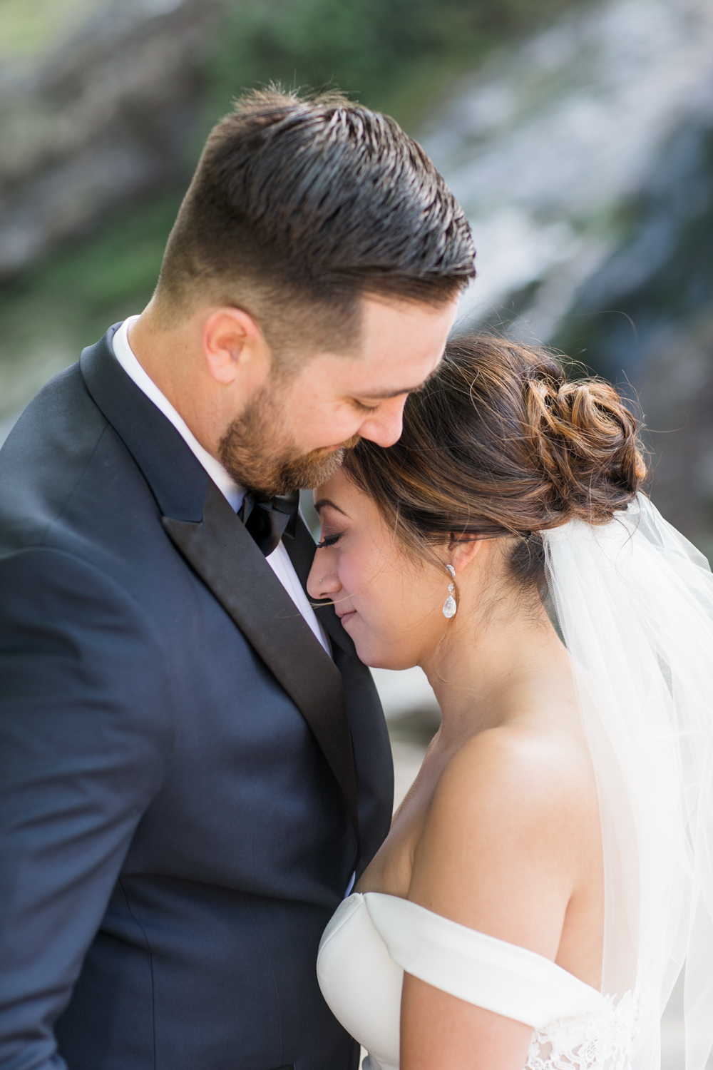 bride and groom portrait close together showing a short veil of the bride and an up style hair do