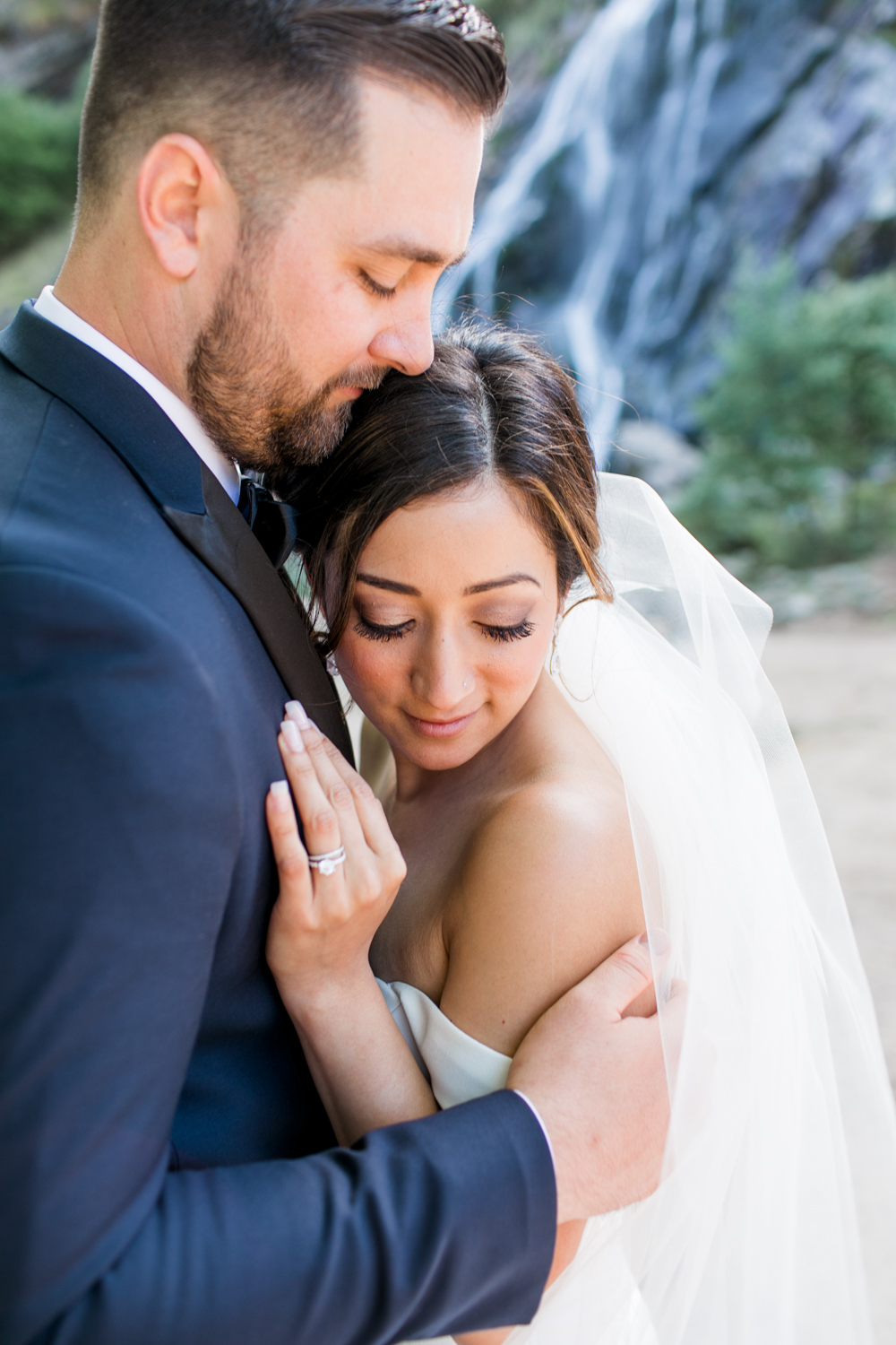 Bride and groom snuggled together with a hint of a waterfall in the background the groom is kissing the bride's head