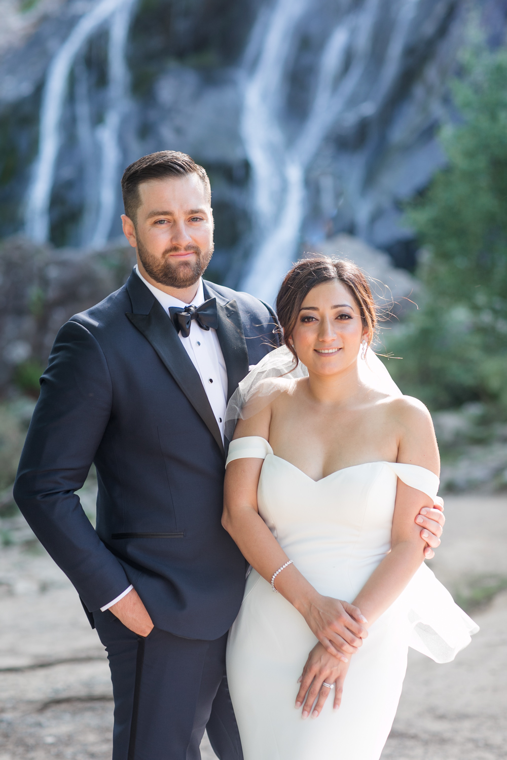 bride and groom posing for the camera wearing black tux with a bow tie and a off shoulder wedding dress with a waterfall behind the bride and groom