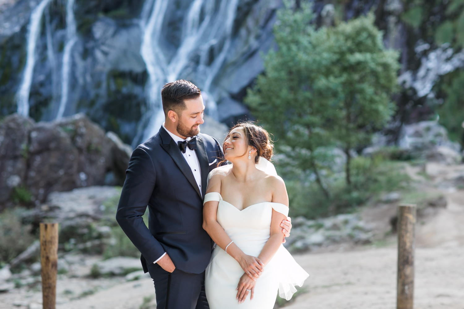 irish waterfall powerscourt in wicklow featuring bride and groom looking at each other wearing elegant black tie wedding gowns