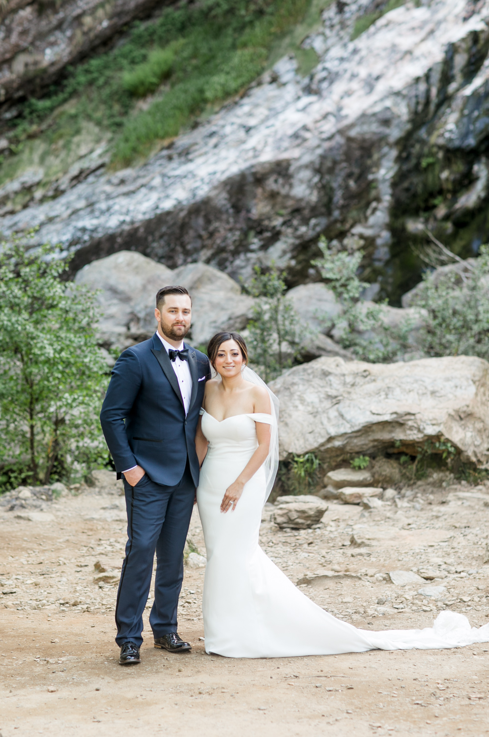 bride and groom standing staring into the distance with a rocky background where the waterfall is located in ireland