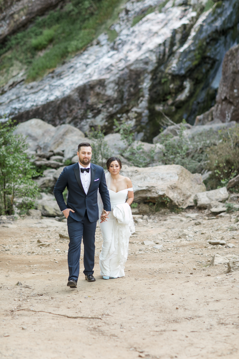 bride and groom walking photograph on their elopement day in ireland at powerscourt waterfall in wicklow