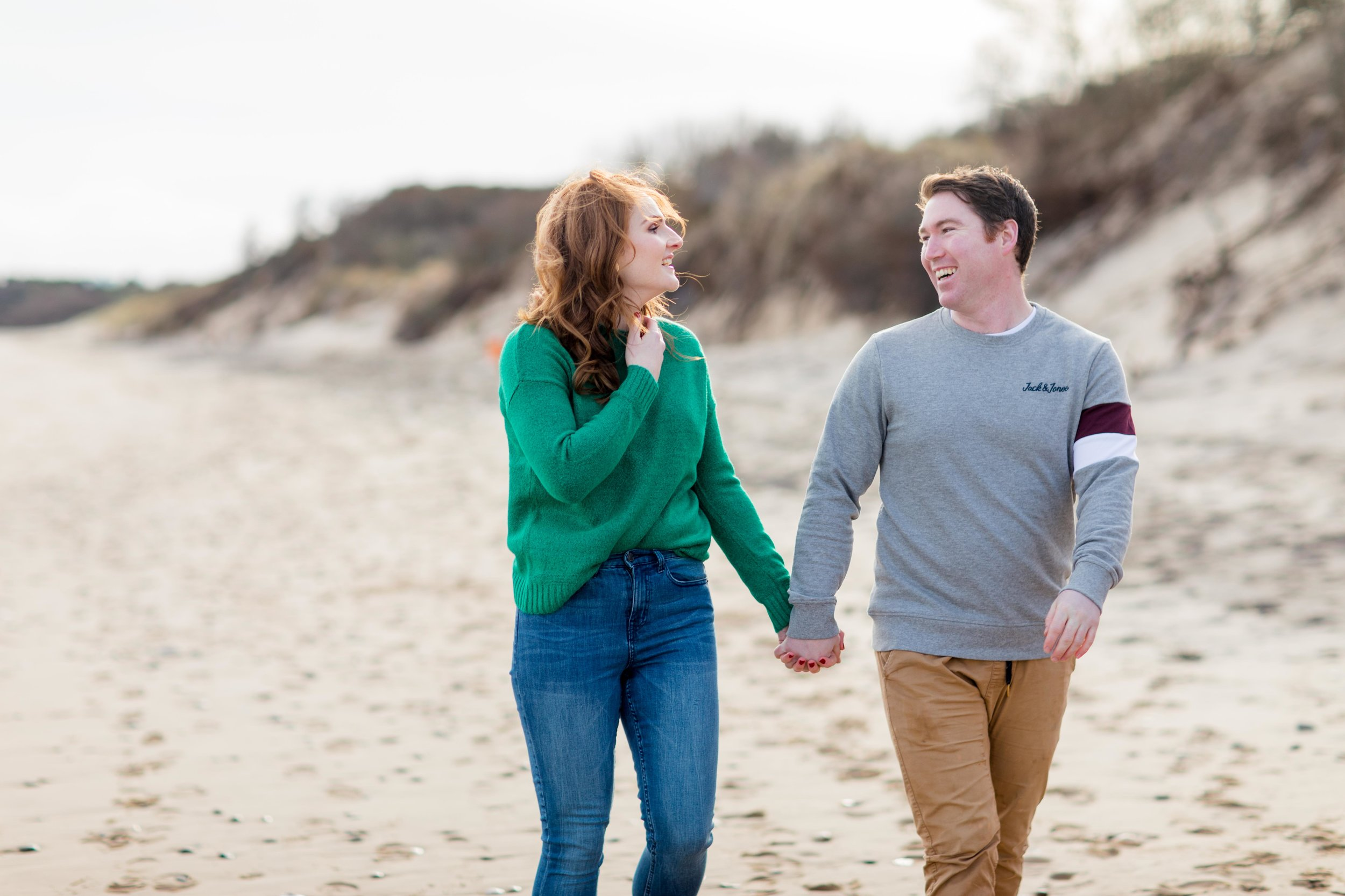 a photoshoot of a couple walking on a sandy beach holding hands in brittas bay in ireland a woman is wearing a green jumper and jeans with red hair and a man is wearing khaki jeans and a grey jumper