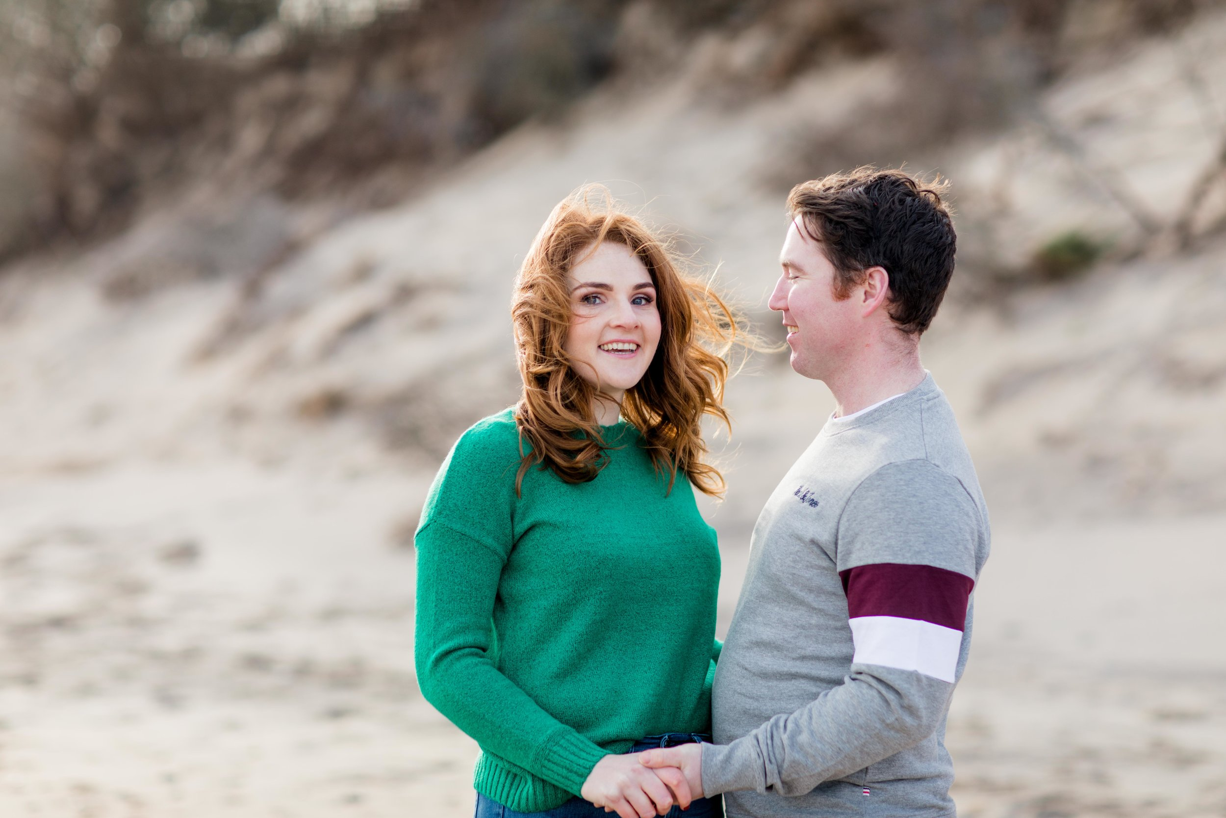 a photoshoot of a couple on a sandy beach wearing a green jumper and a grey jumper holding hands with red hair in ireland on brittas bay