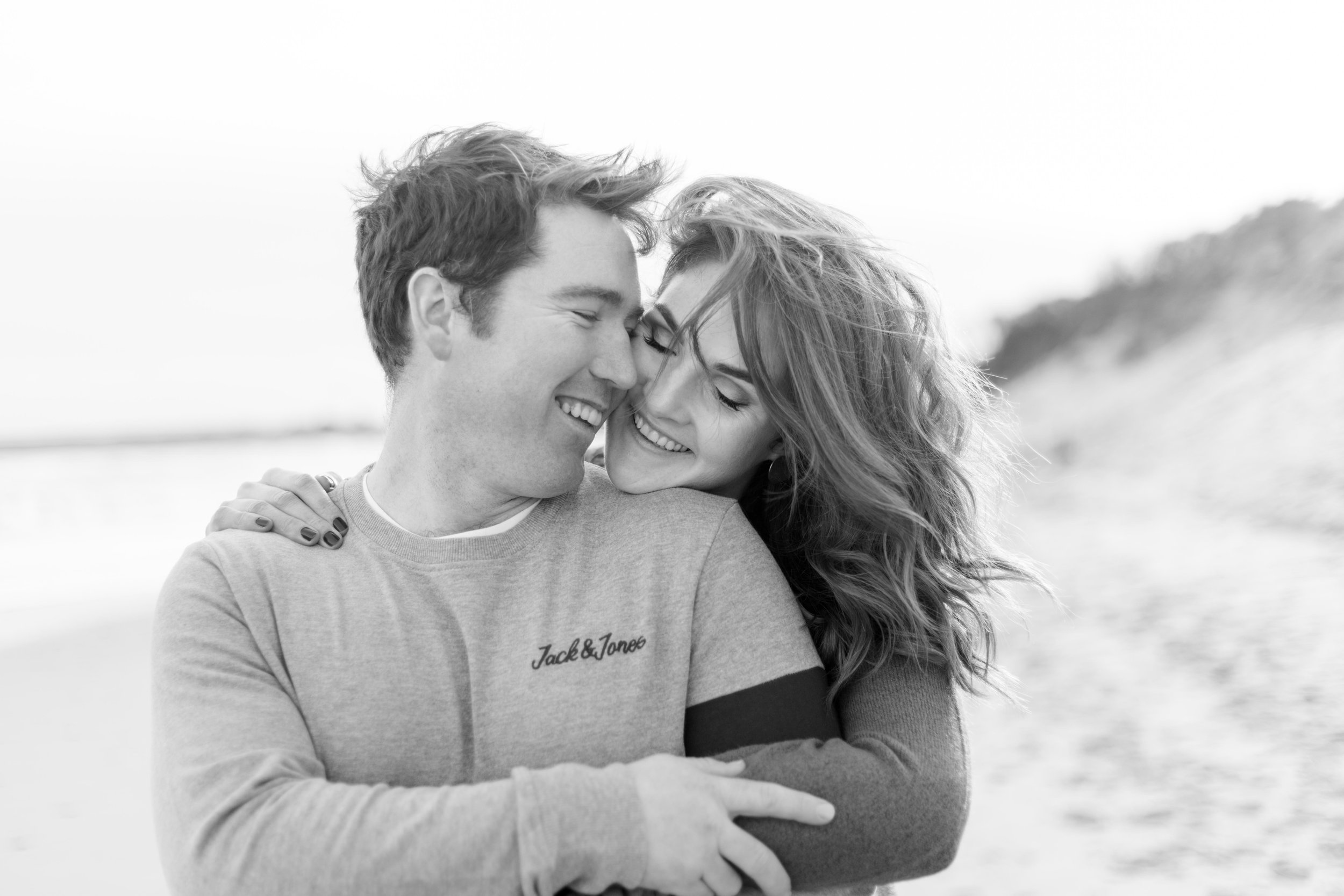 a couple laughing and hugging on a sandy beach