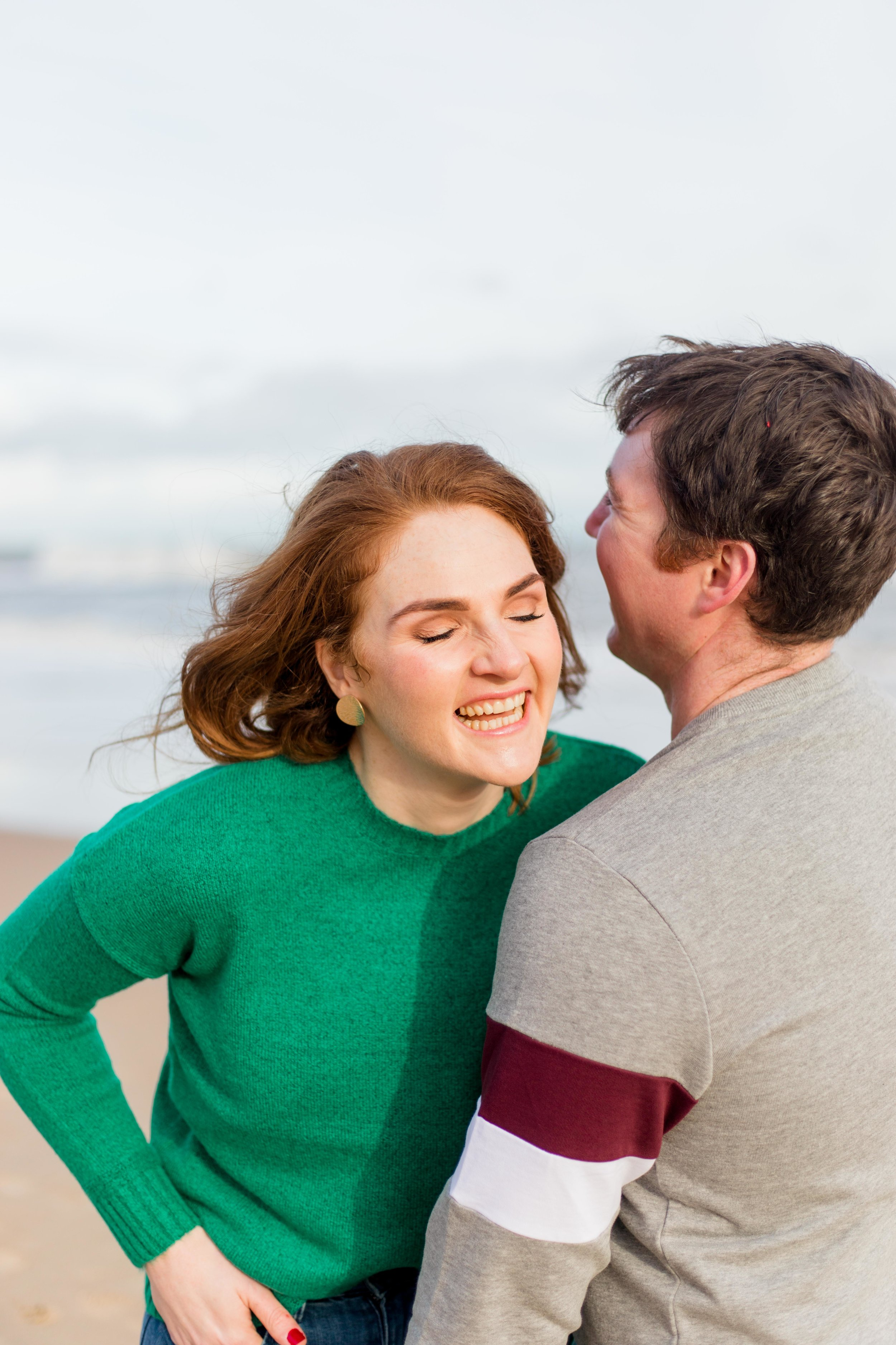 woman wearing a green jumper is being tickled by a man in grey jumper on a sandy beach posing for an engagement photoshoot at brittas bay in ireland