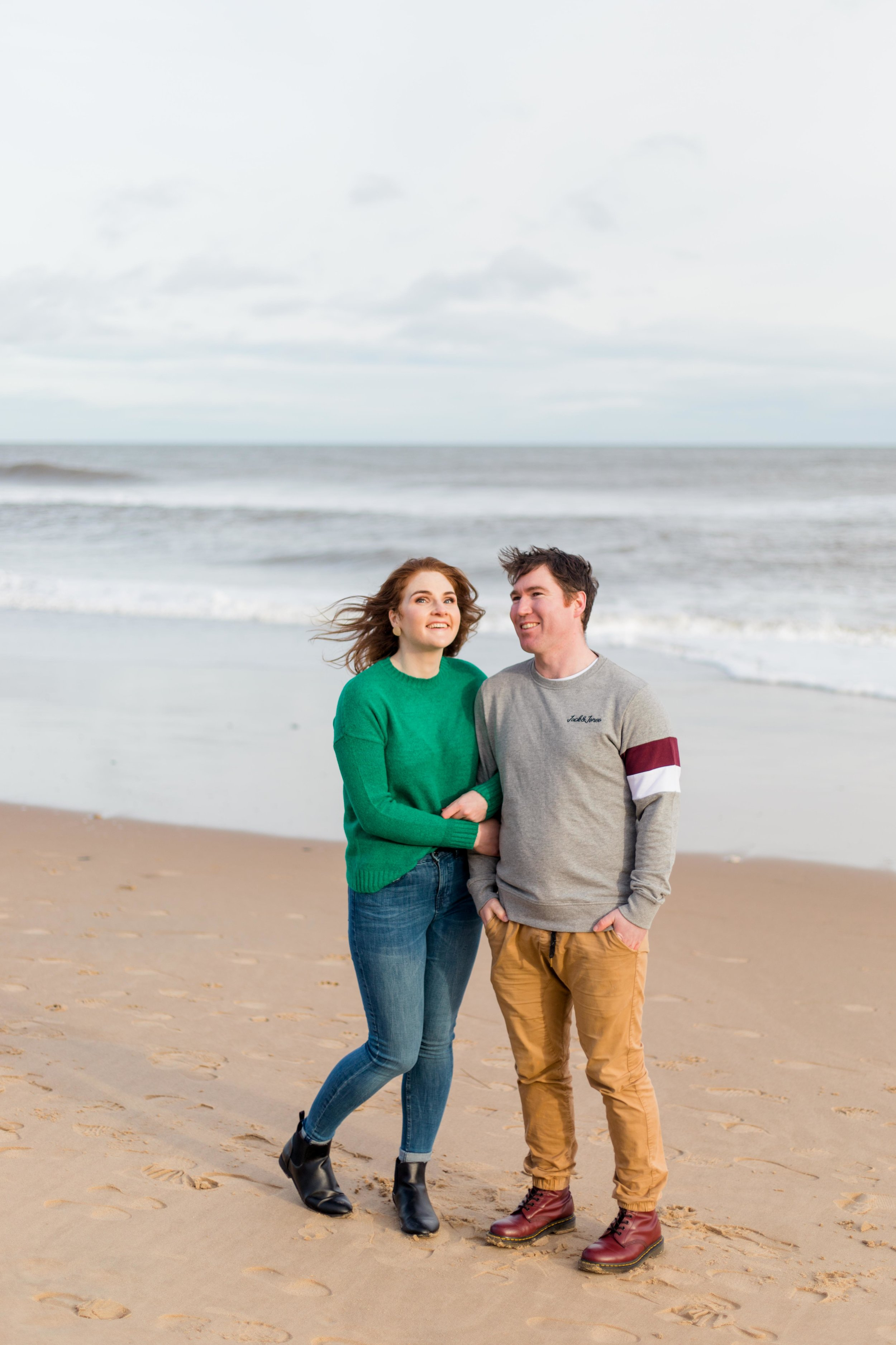 man and woman posing for an engagement photoshoot on a sandy beach wearing a green knit jumper and blue jeans with black boots and man grey jumper and khaki chinos