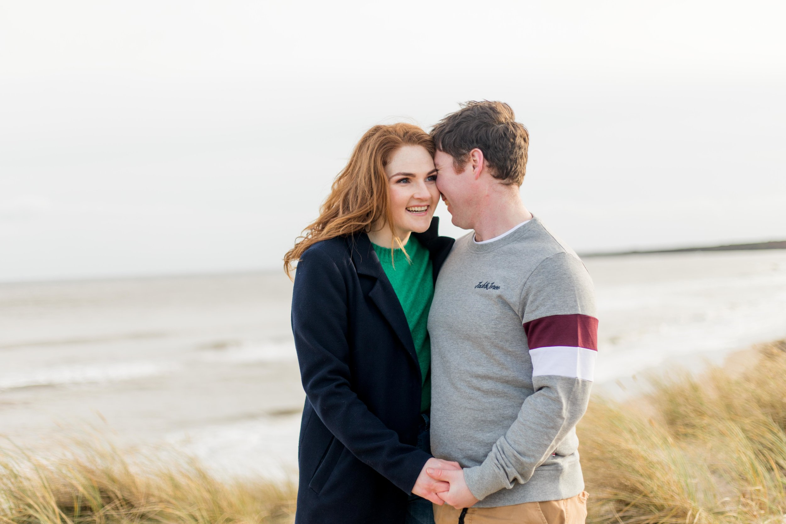 a couple posing for a photoshoot on a sandy beach a woman is dressed in green knit jumper and a black coat with red hair smiling at her fiancee in ireland