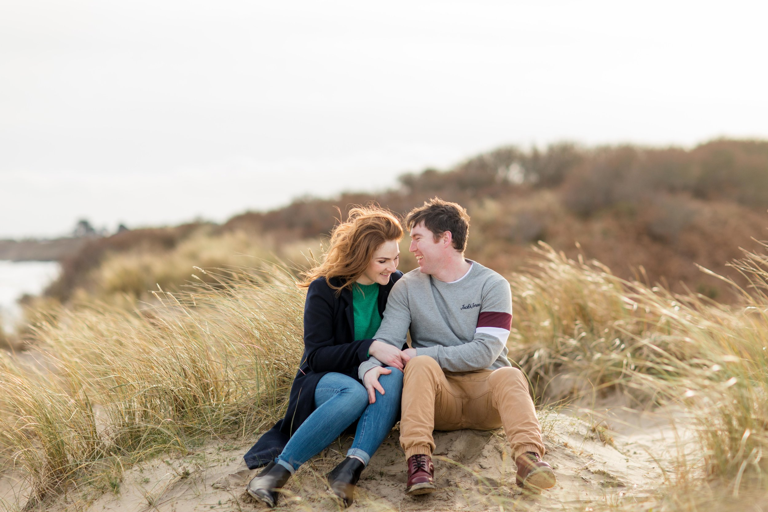 a couple posing for an engagement photoshoot sitting down on a sand dune in brittas bay beach in ireland