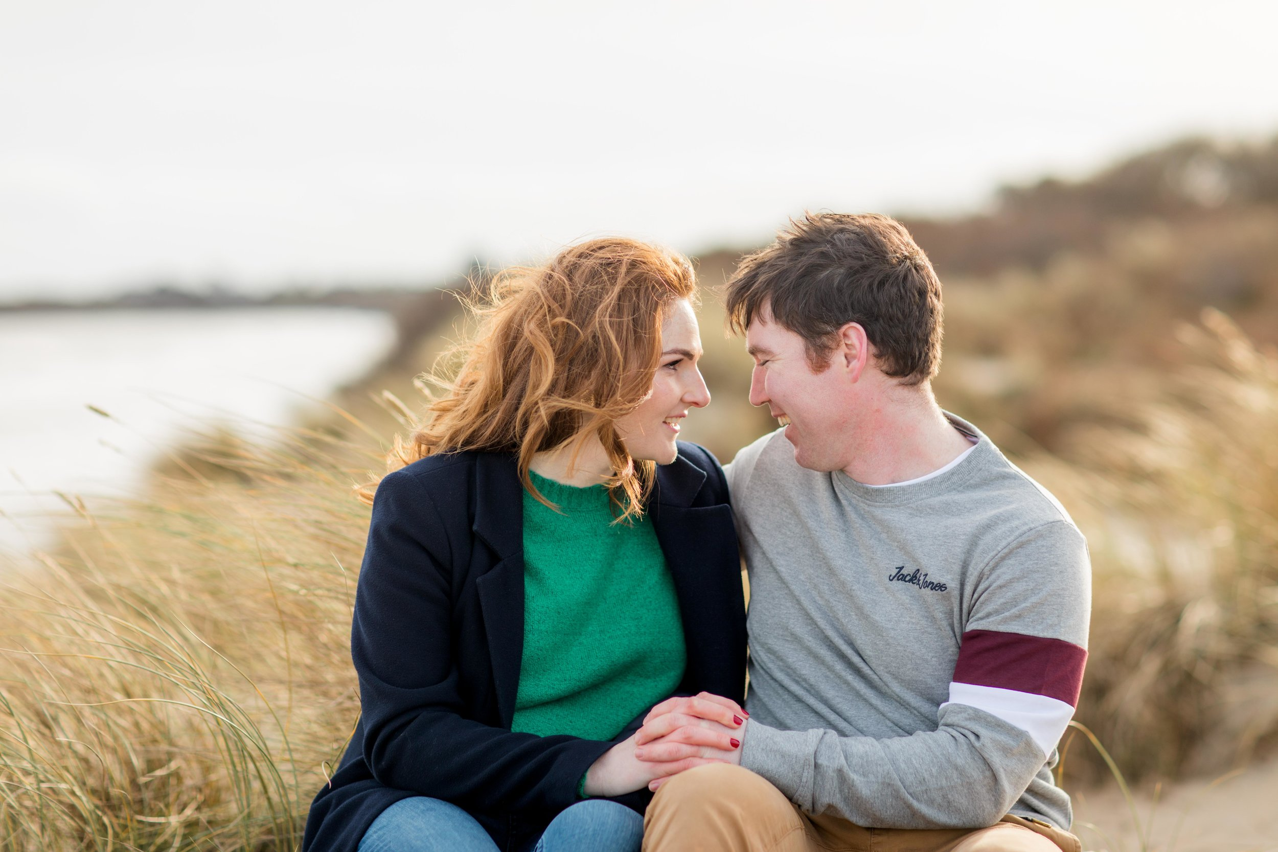 a couple sitting down on a sand dune in britta's bay ireland during a golden sunset with wind blowing through her red hair