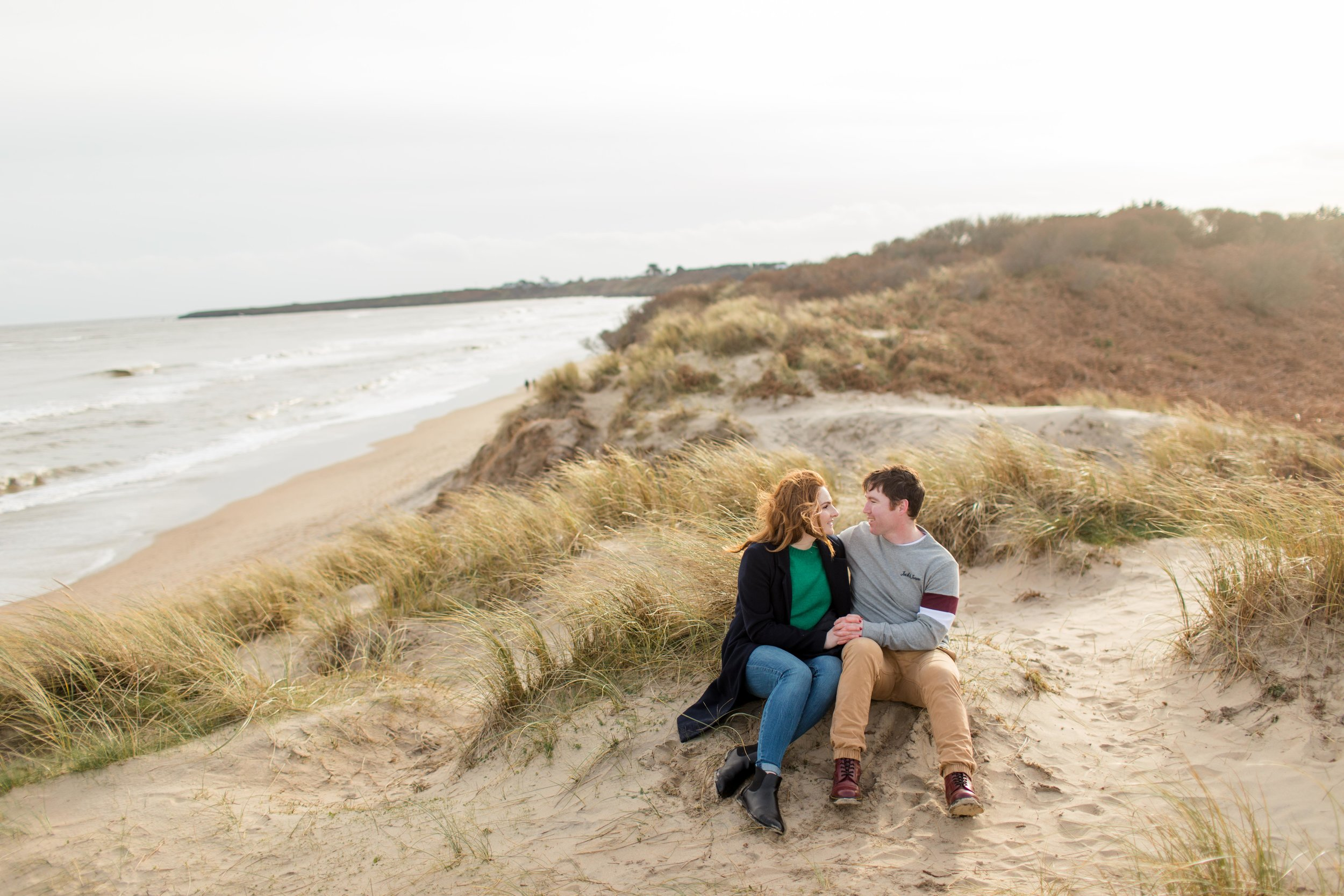 a landscape photograph of a couple sitting on a sand dune with the irish sea and brittas bay beach in the background posing for their engagement photoshoot