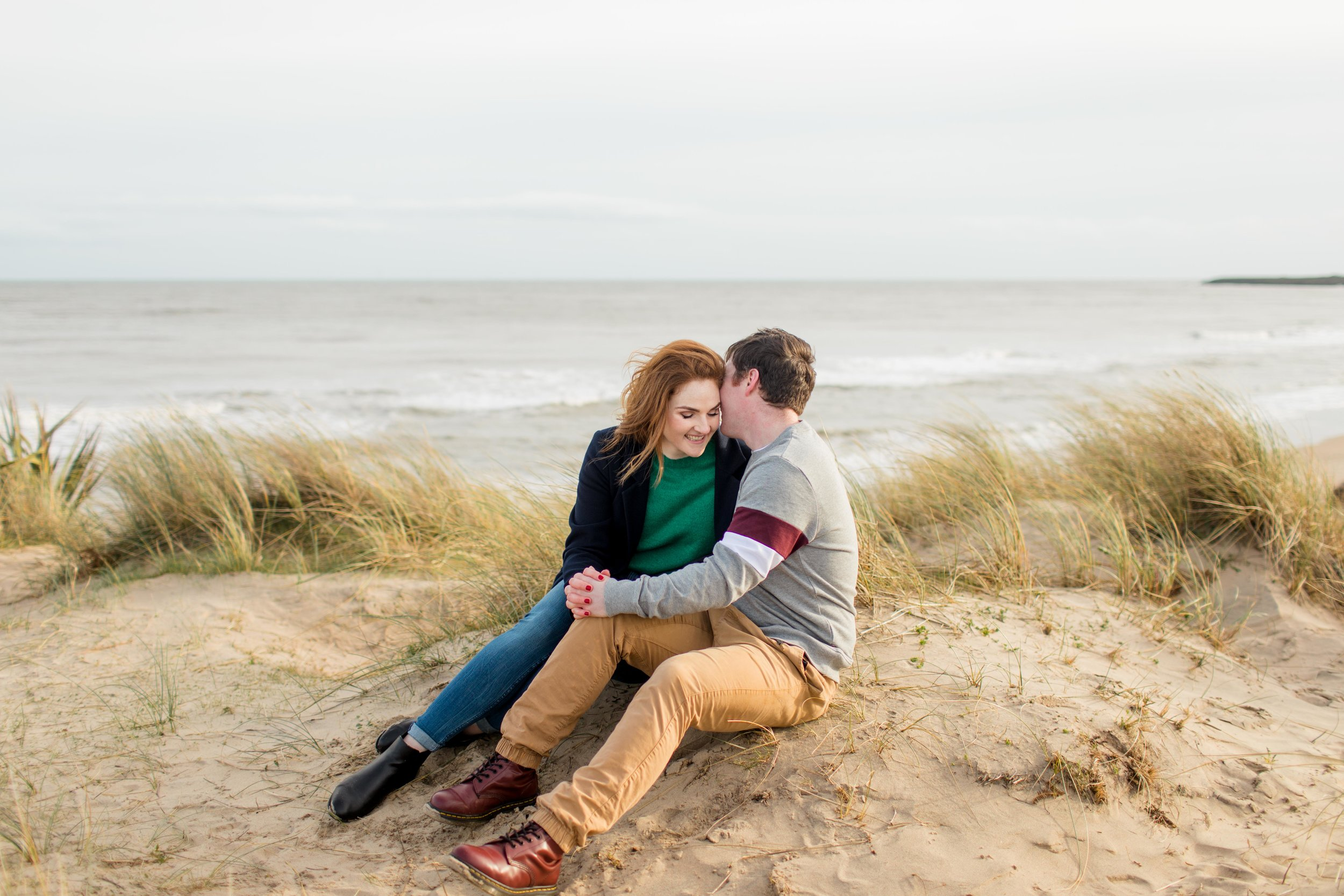 a couple on a sand dune in brittas bay in wicklow in ireland posing for a photoshoot a guy kissing his fiancee on the temple