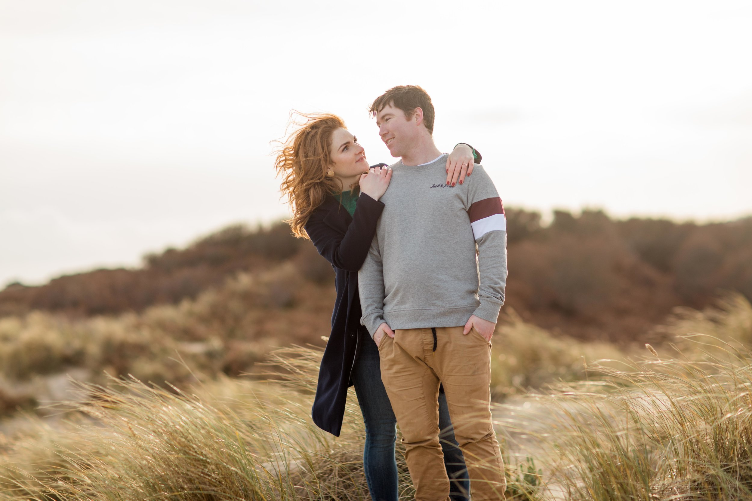 a couple posing for their engagement session on a sandy dune in brittas bay during a sunset with wind blowing through her red hair while she is hugging her fiance
