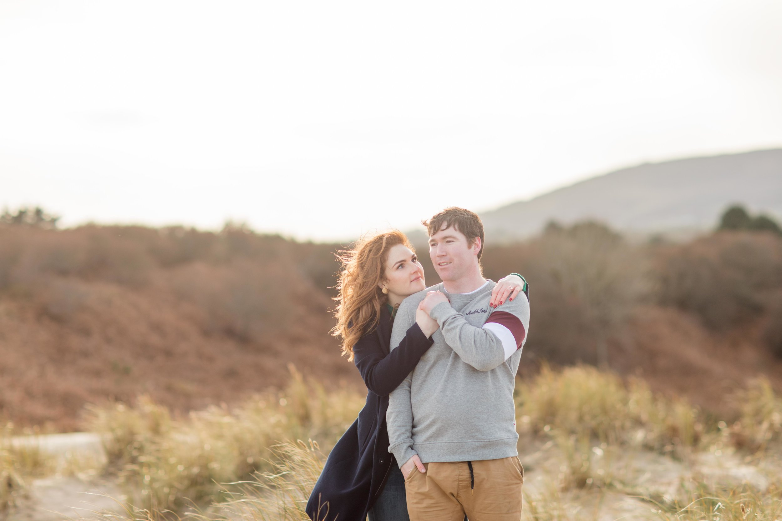 a sandy dune in brittas bay in ireland with a couple posing for a photoshoot and hilly background her hair red in a setting sun