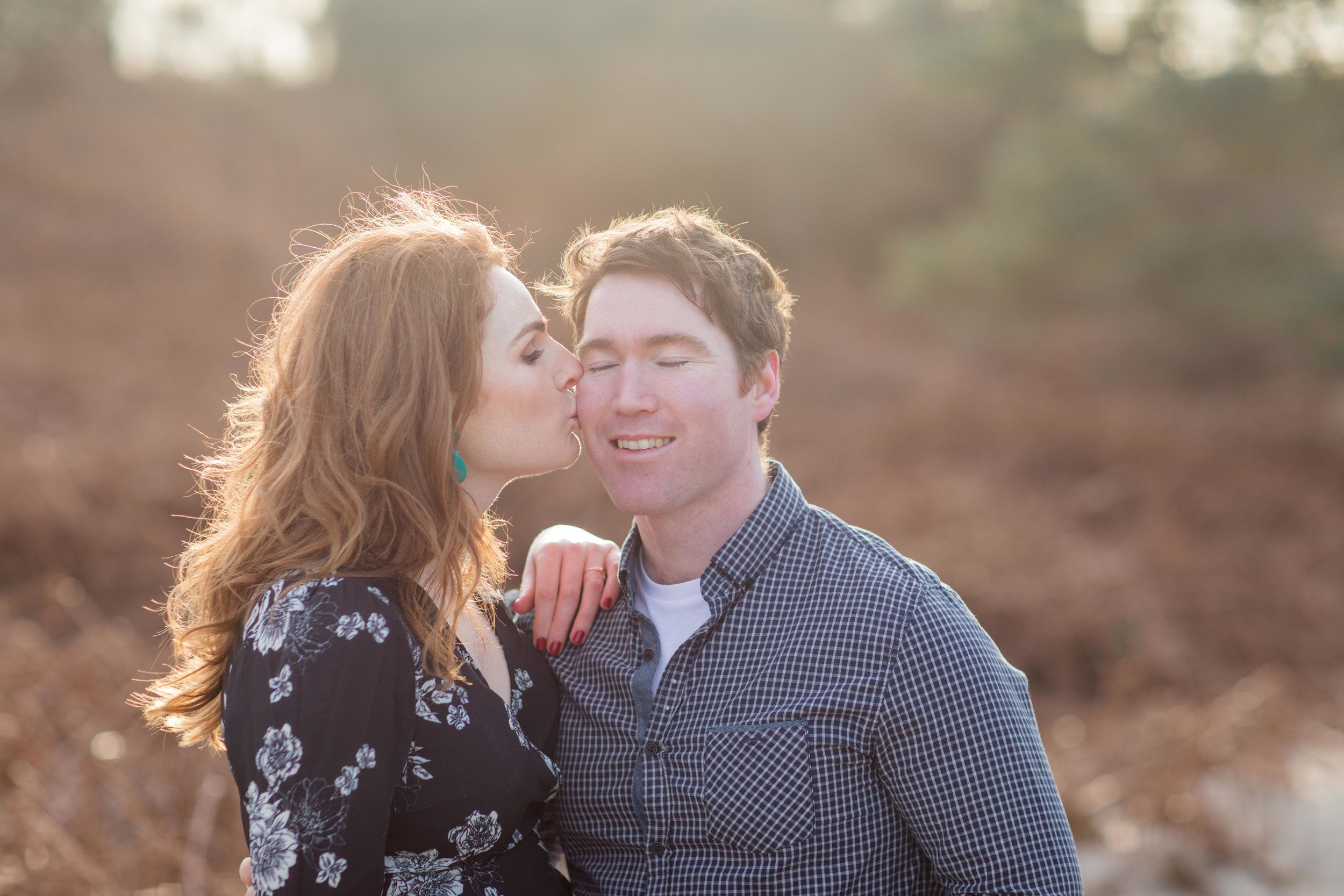 a photoshoot in ireland's setting sun a woman is kissing her future husband on the cheek she has red hair green earrings wearing a black dress with white flowers and red nail varnish