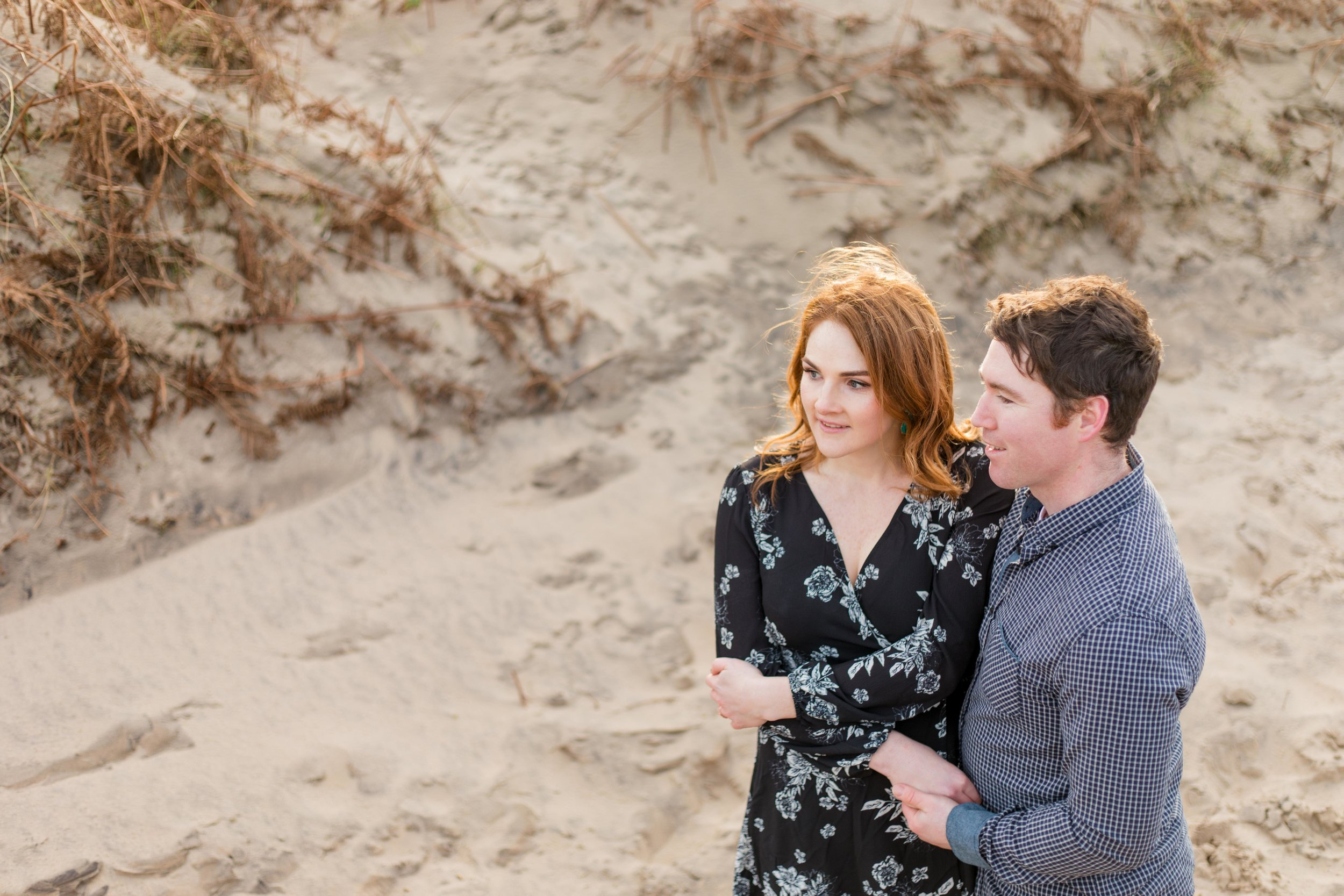 a red headed woman holding hands with her future husband posing for an engagement photoshoot with shoulder length hair wearing a knee length black dress with white flowers on a sandy beach in ireland