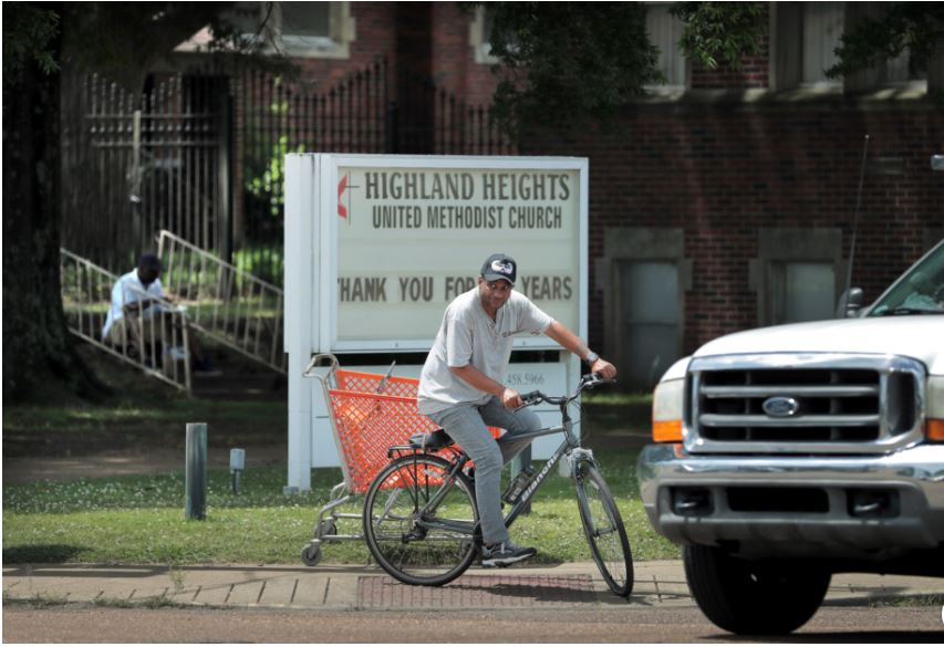 A cyclist waits for traffic to clear at the corner of Highland and Summer in front of the Highland Heights United Methodist Church, which recently closed after 106 years. The Memphis United Methodist Conference, which owns the property, is hoping that the church building's corner location will be an asset while trying to sell. (Jim Weber/Daily Memphian)