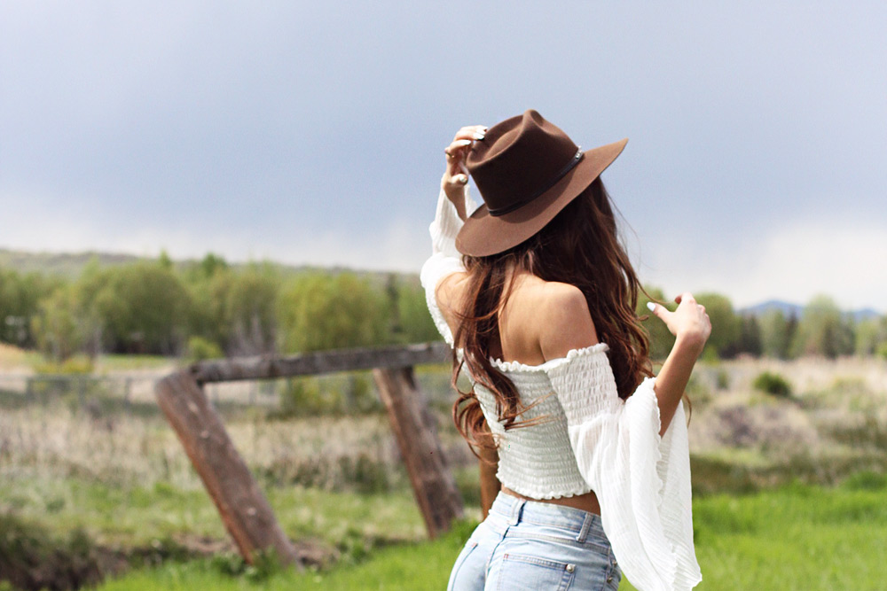 A girl wearing a cowboy hat. Denim shorts and white off shoulder top outfit.