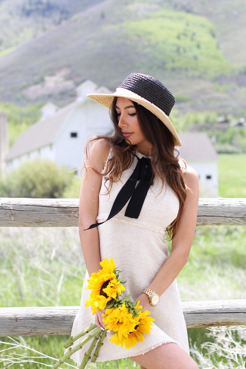 Ulia Ali holding sunflowers and wearing ZARA dress.