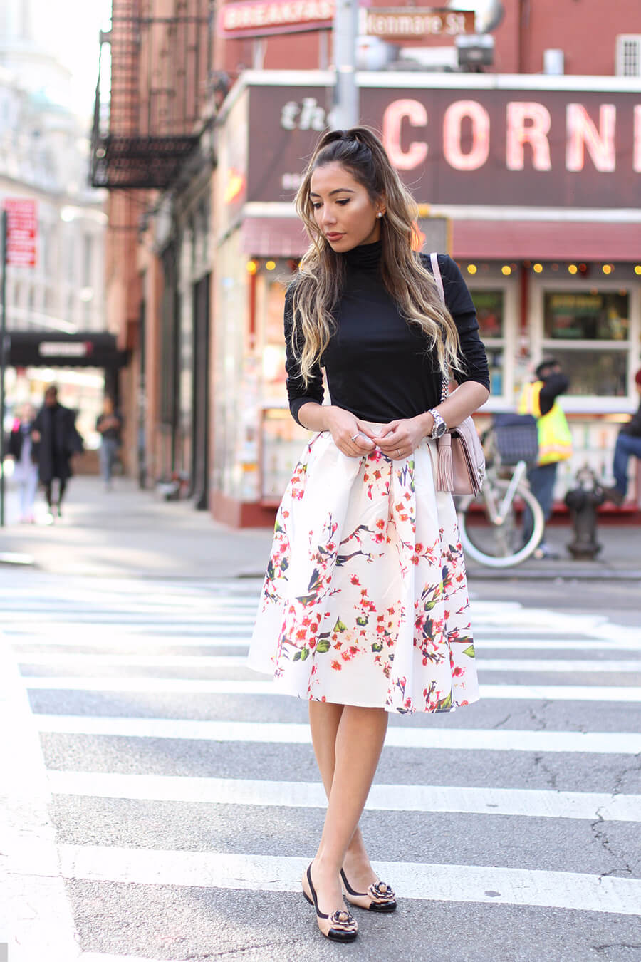 Ulia Ali in black turtleneck, floral skirt and pastel accessories.