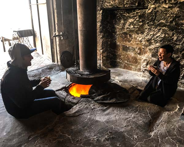 A tonir is a pretty great place to keep warm on cold mornings. Here, Ara and Marie Lou warm up with  soorj  and the fire on our visit to Argel.