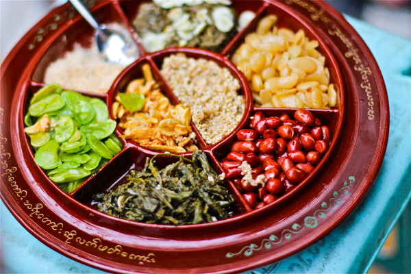 laphet (fermented tea leaf) served with crunchy bits: sesame seeds, peanuts, fried beans, and fried garlic