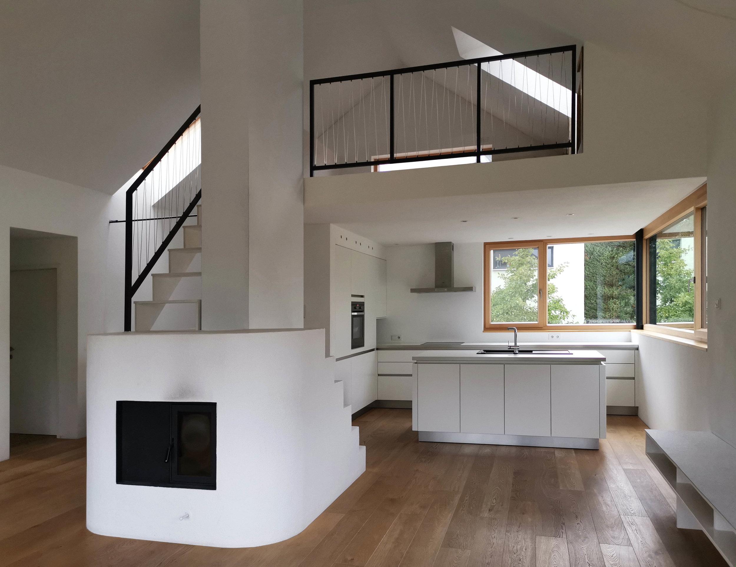 IMST, Wohn- und Essbereich mit Kaminofen als Treppe zur Galerie
