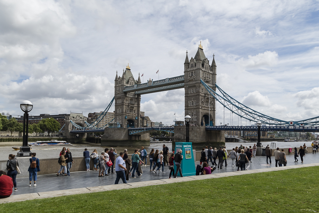 Milling crowds satisfied after just seeing the bascules raise at Tower Bridge
