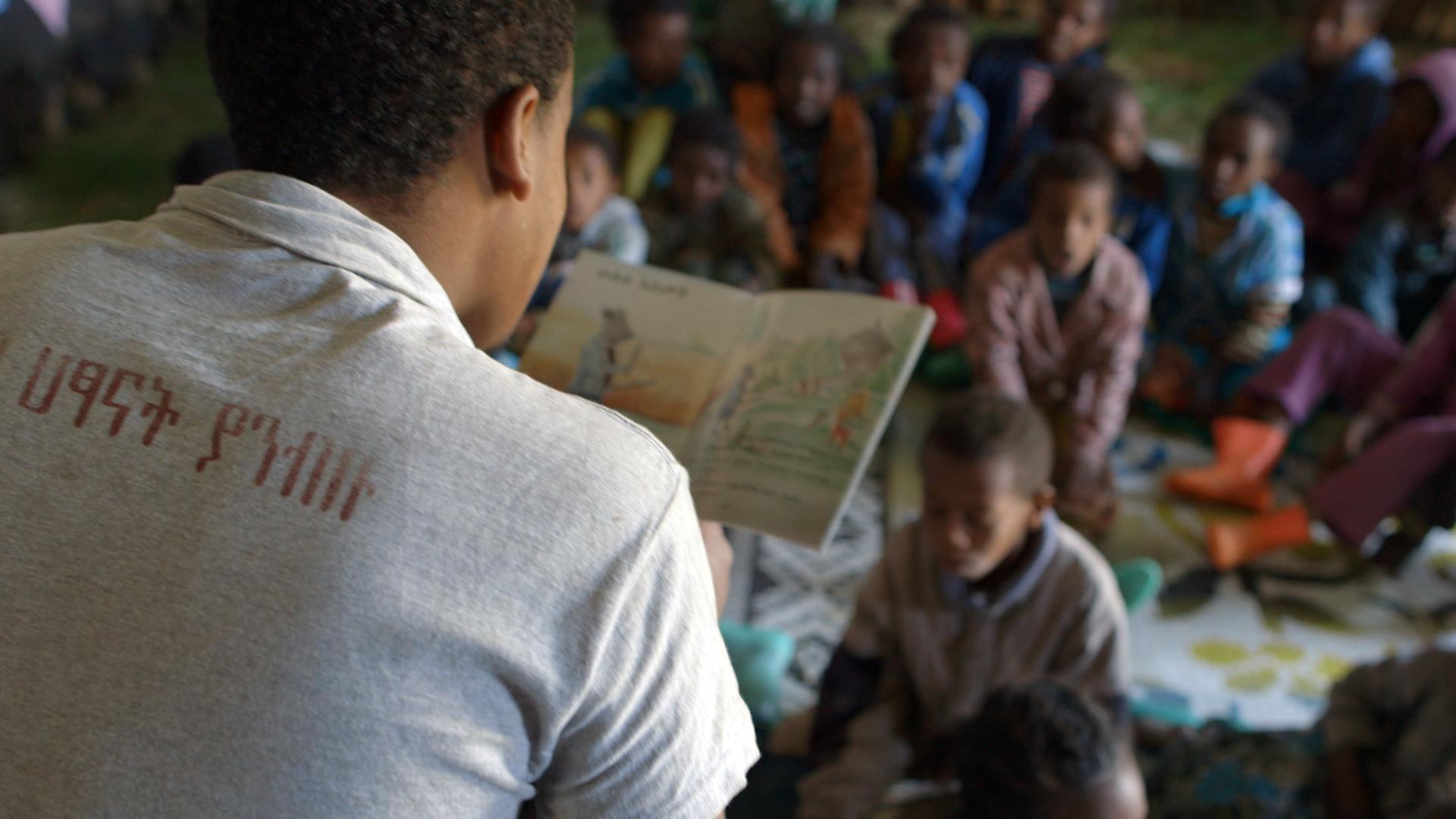 Belihu reads to children. (Photo credit: Max Greenstein / World Vision)