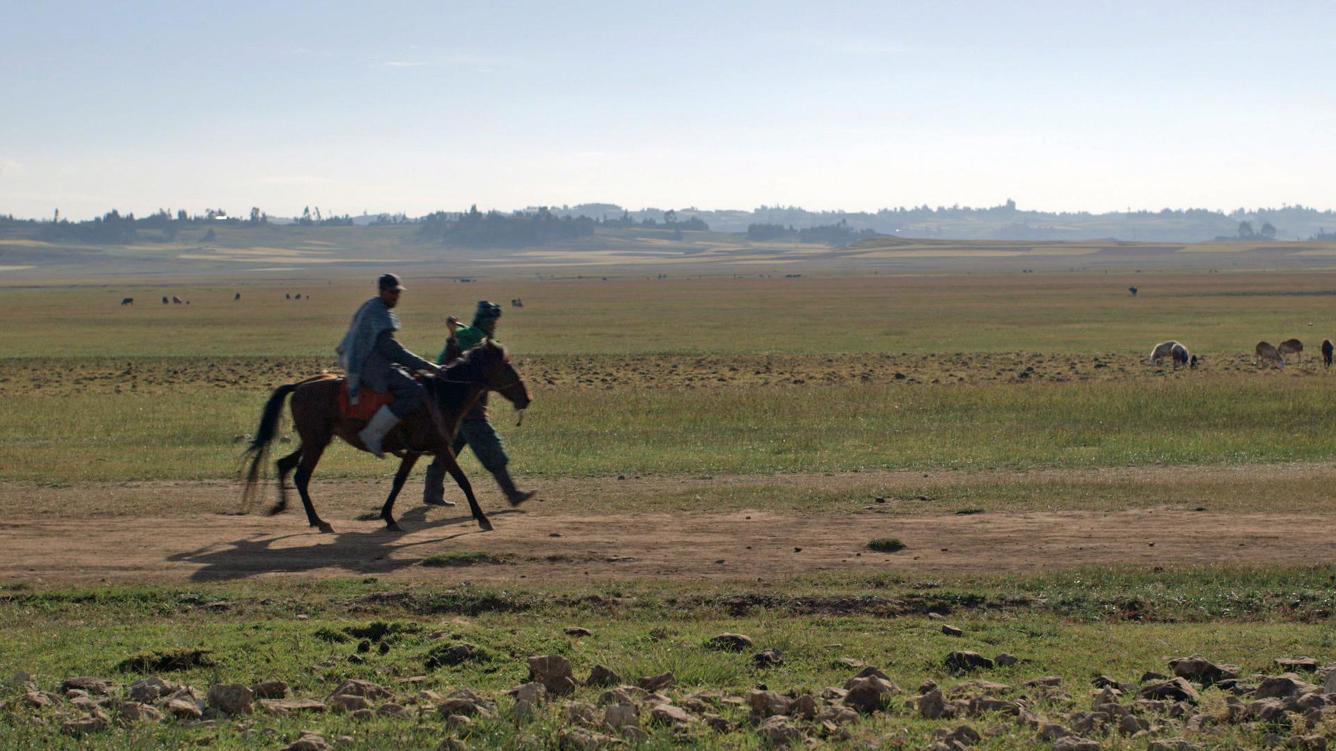 Men on horseback ride across landscape (Photo credit: Max Greenstein / World Vision)